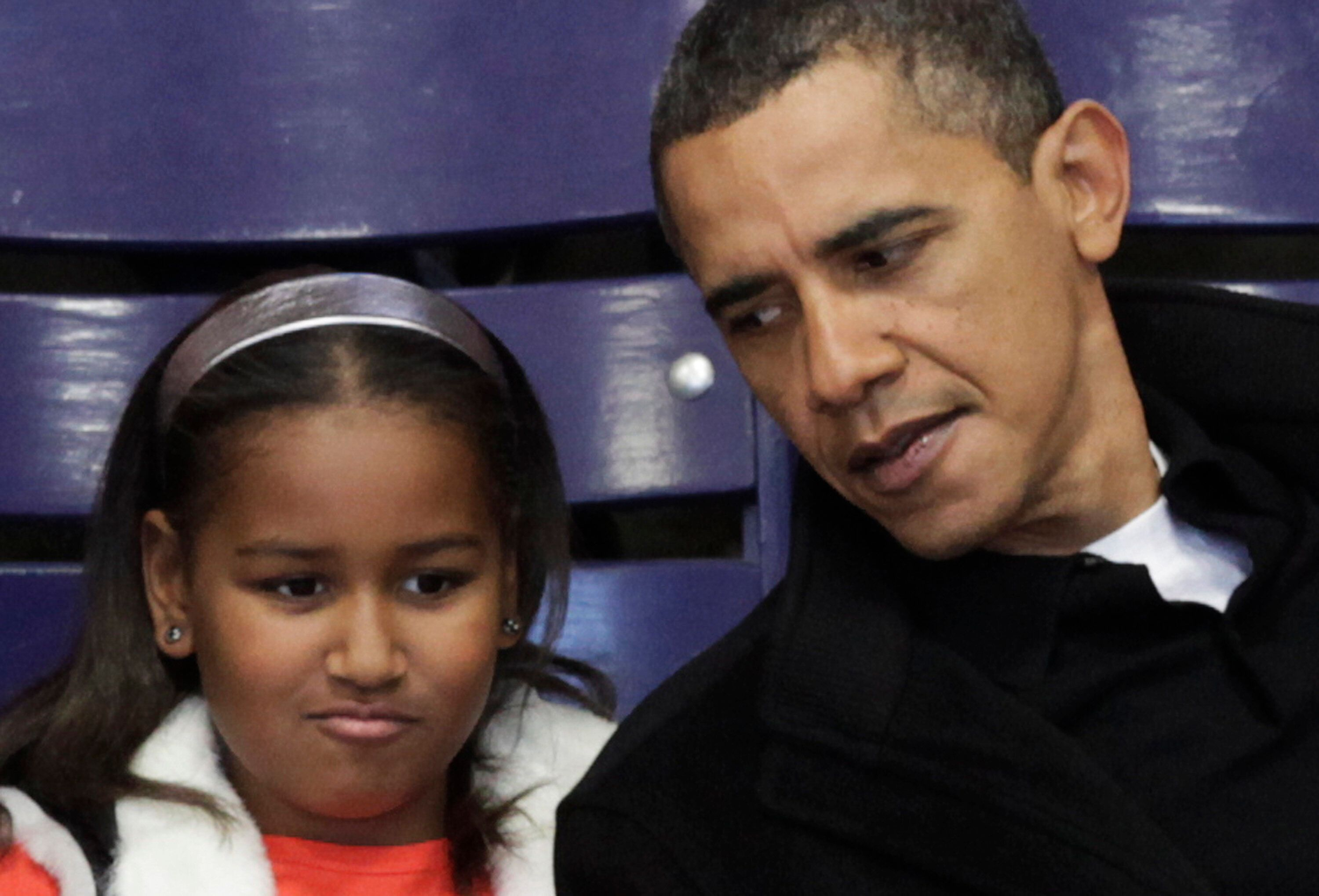 Then-President Barack Obama talks to his daughter Sasha during a Howard University basketball game in 2010, around the time h