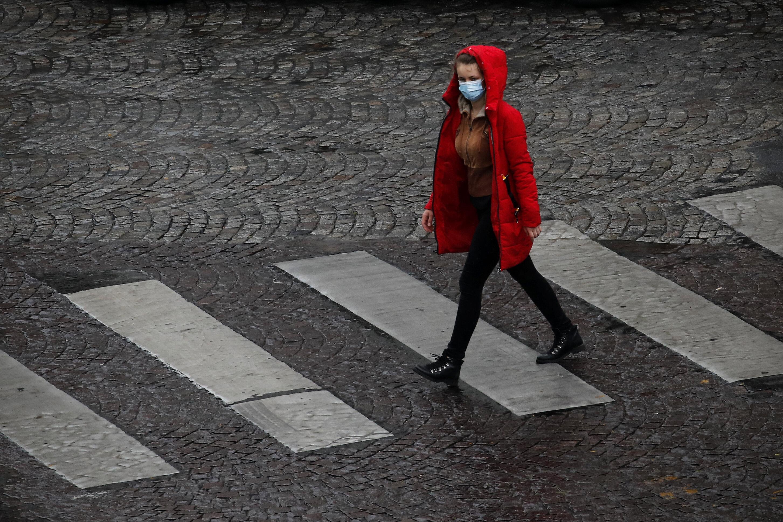 Une passante portant un masque à Paris pendant le confiement en mai 2020 (AP Photo/Christophe