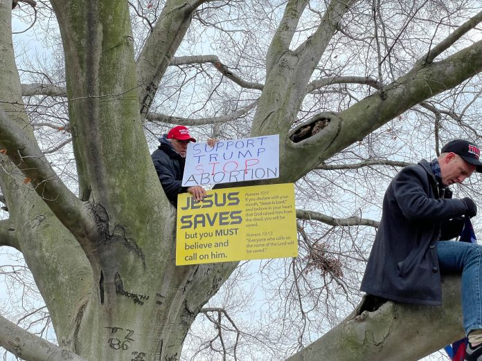 """A man carries a sign reading """"Jesus Saves"""" during an insurrection at the U.S. Capitol on Jan. 6, 2021."""