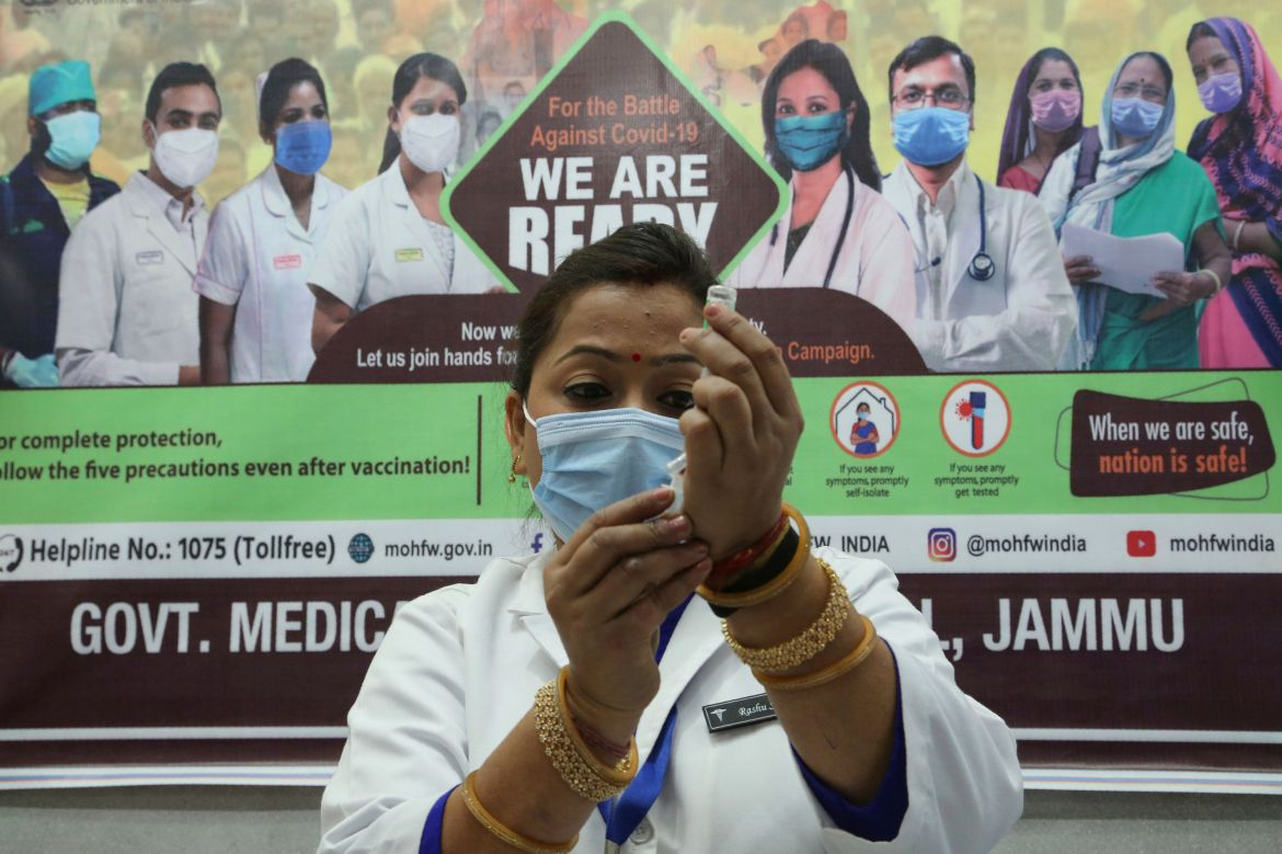 A health worker prepares to administer COVID-19 vaccine to a doctor at a government Hospital in Jammu, India, Saturday, Jan.1
