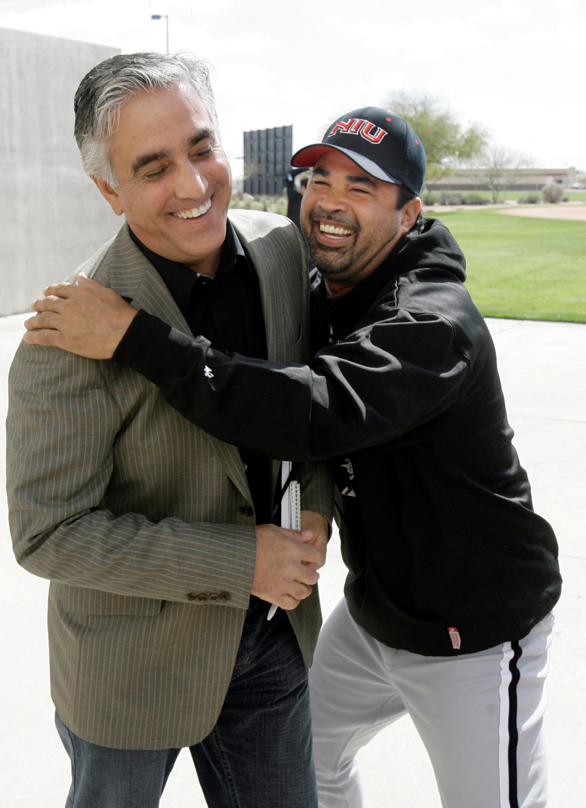 Chicago White Sox' manager Ozzie Guillen, right, jokes with ESPN's Pedro Gomez after a news conference in 2008.