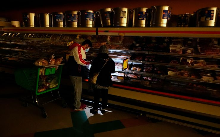 Customers use the light from a cellphone to look in the meat section of a Dallas grocery store on Feb. 16. Though the store l