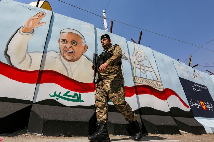 A member of the Iraqi forces walks past a mural depicting Pope Francis waving next to an Iraqi national flag drawn on a blast