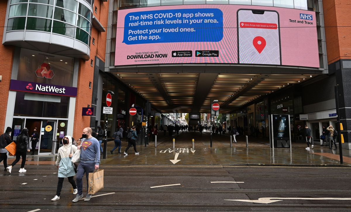 Shoppers pass beneath an electronic sign promoting the NHS Covi-19 app, outside the Arndale Centre in