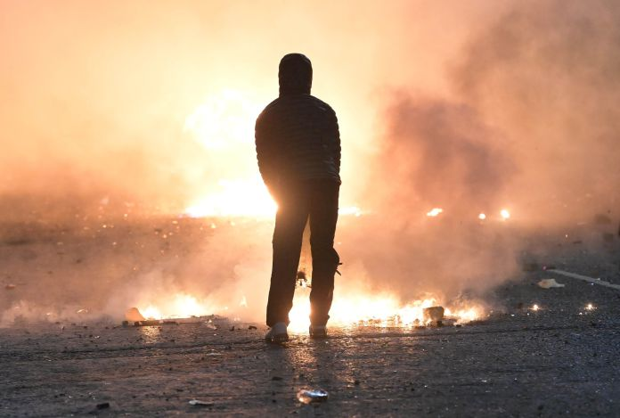 A person looks on as debris burns during clashes at the Springfield Road and Lanark Way interface in
