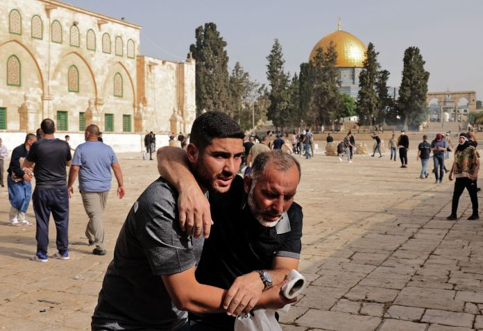 A Palestinian man helps a wounded fellow protester amid clashes with Israeli security forces at Jerusalem's Al-Aqsa mosque co