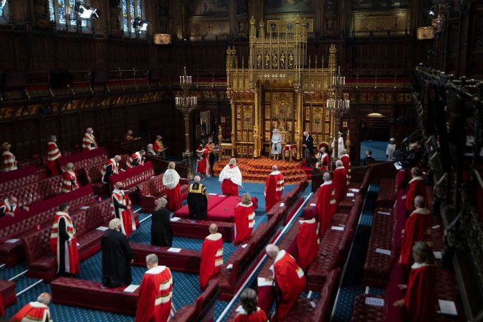 Queen Elizabeth II reacts after reading the Queen's Speech on the The Sovereign's Throne in the House of Lords chamber.