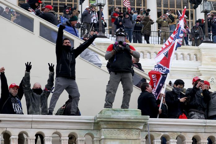 Russ Taylor (middle, in MAGA hat) on the west side of the Capitol during the attack.  Another potential defendant, wearing a SIMI