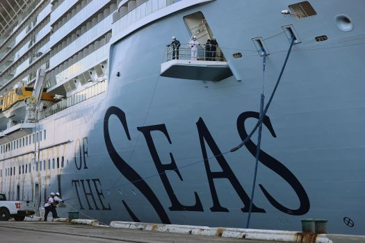 Dockworkers and crew members use ropes to tie the Royal Caribbean's Odyssey of The Seas to its berthing spot at Port Ev