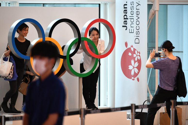 People take pictures with the Olympic rings displayed at the arrival lobby in the Tokyo International Airport in Tokyo on Thu