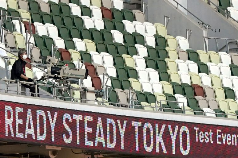 A TV cameraman sits beside empty spectators' seats during an athletics test event for Tokyo 2020 Olympics Games at the Nation