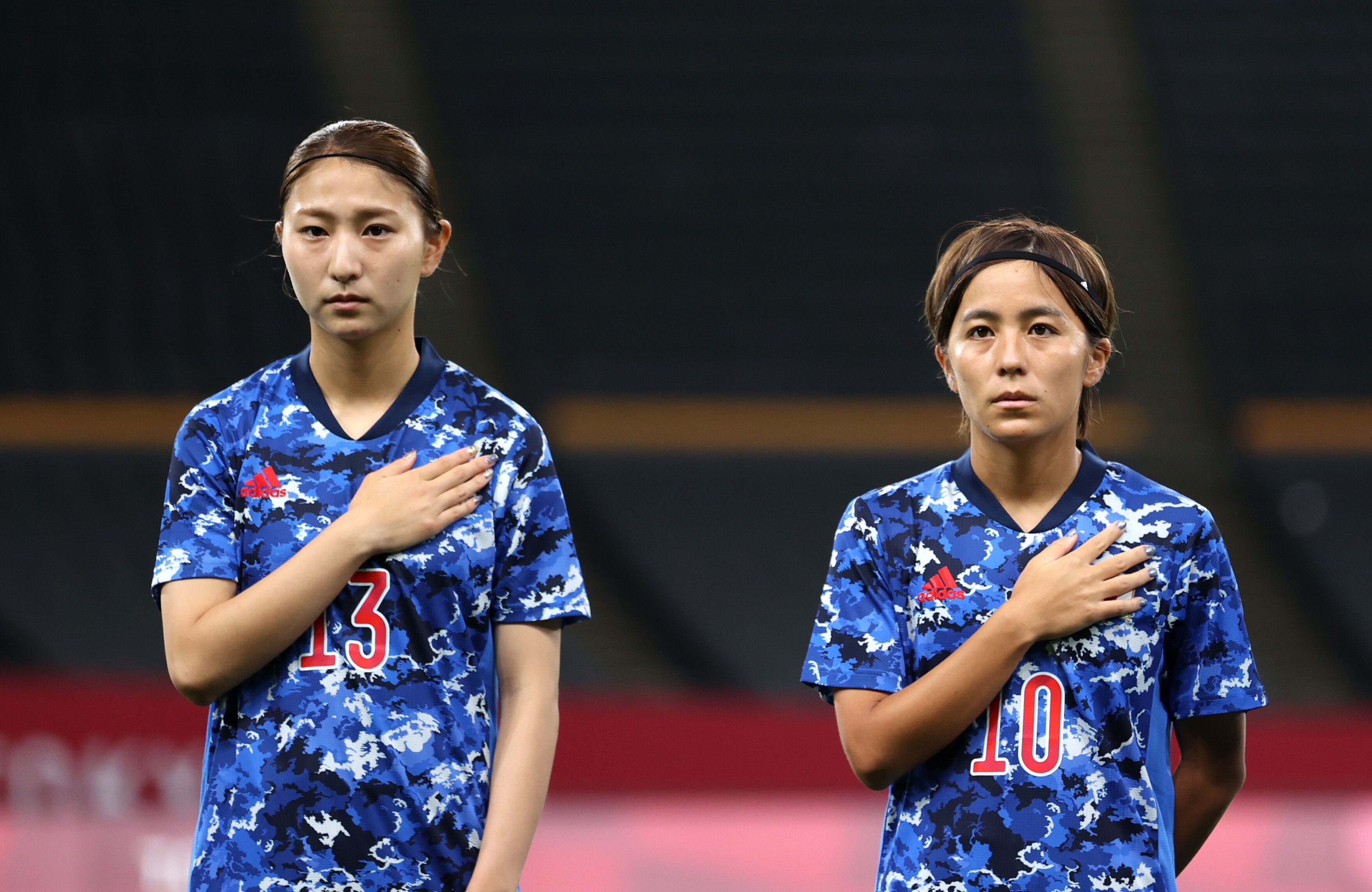 SAPPORO, JAPAN - JULY 21: (L - R) Yuzuho Shiokoshi #13 and Mana Iwabuchi #10 of Team Japan stand for the national anthem prio
