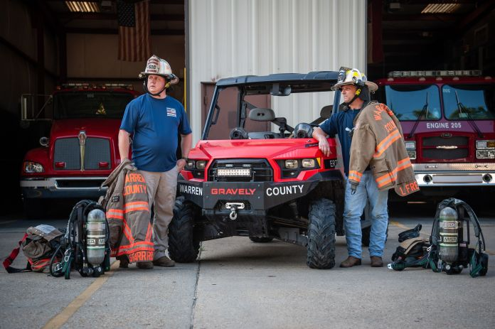 Warren County firefighters Shane Garrard (left) and Lamar Frederick in Vicksburg, Mississippi, in July. They're next to the utility task vehicle they used during the February 2020 gas leak in Satartia. <br /><strong>Rory Doyle for HuffPost.</strong>
