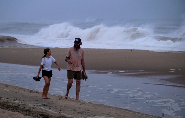 Ryan Madigan, and his daughter Charolette Madigan, 11, of Cold Spring Harbor, N.Y., stand along a beach in Montauk, N.Y., Sat