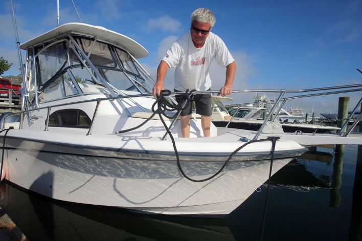 Rob Edwards, from Newport, R.I., adds extra lines to secure his boat at the Goat Island Marina, Saturday, Aug. 21, 2021, in N