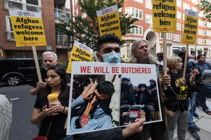 Demonstrators including Afghan people protesting outside the Home Office demanding a safe passage to...