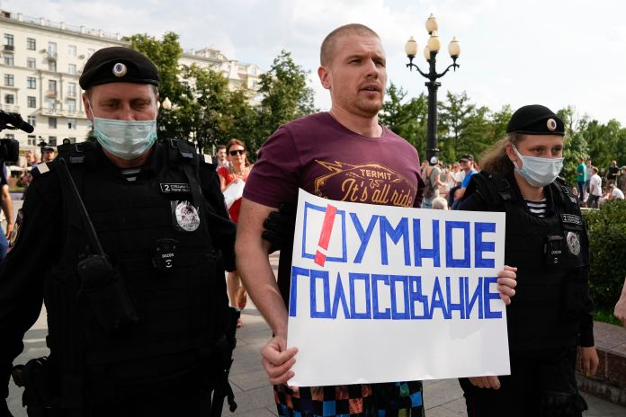 """Russian police detain an opposition activist with a poster reading """"Smart voting"""" during an anti-vaccination protest in the c"""
