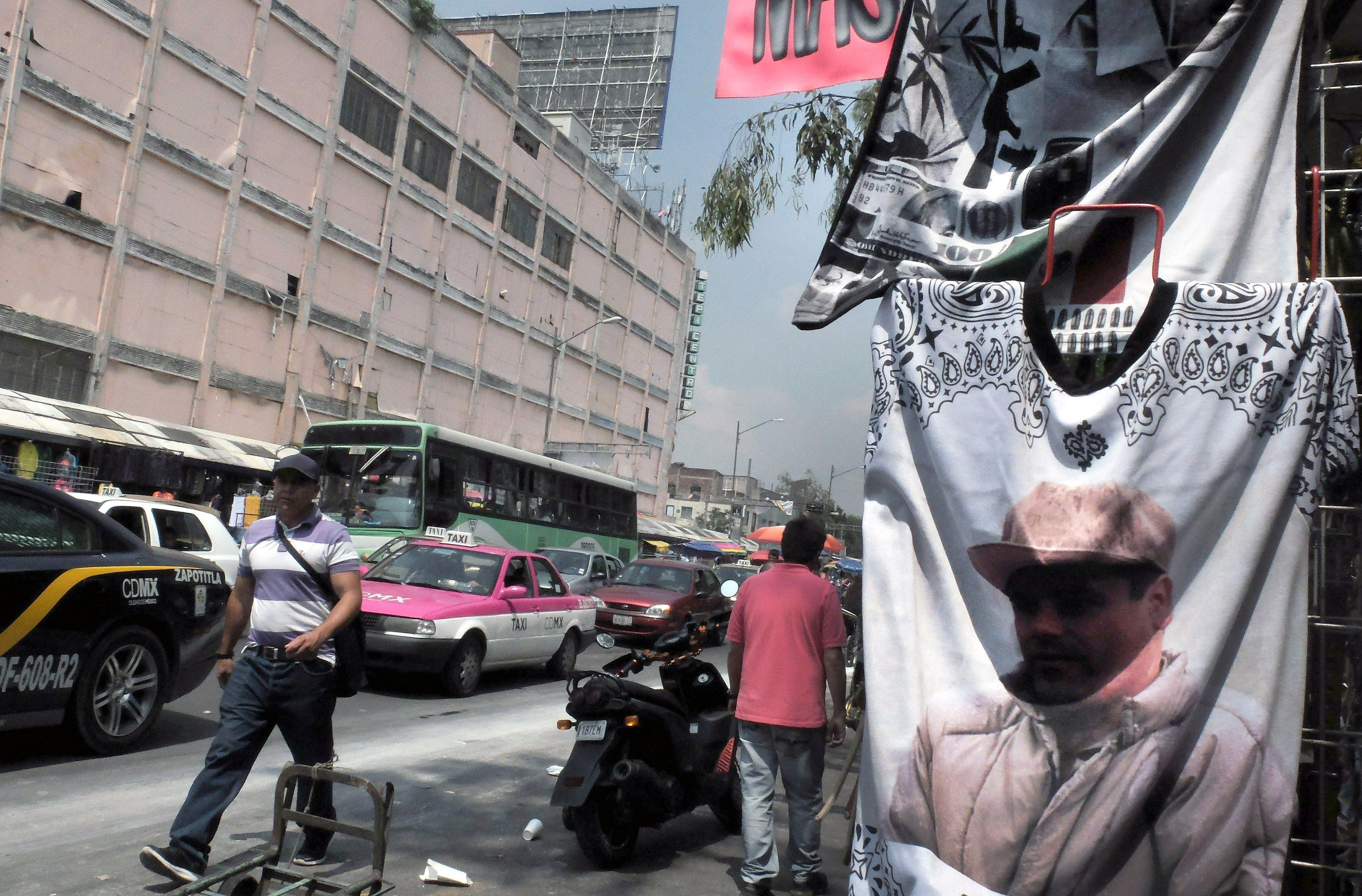 """<span class='image-component__caption' itemprop=""""caption"""">Mexican drug lord Joaquín """"El Chapo"""" Guzmán, pictured here on a T-shirt in Mexico City, is still at large after escaping from his jail cell in July.</span>"""