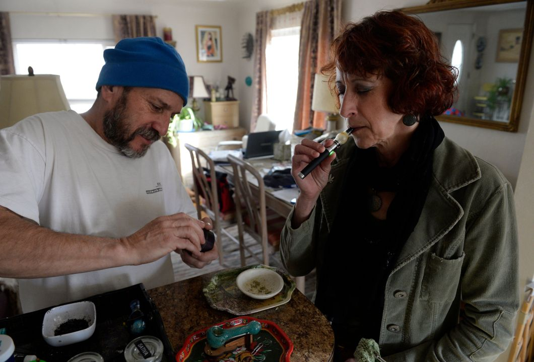 """<span class='image-component__caption' itemprop=""""caption"""">Colorado medical marijuana patient Teri Robnett, right, uses a vape pen to manage chronic fibromyalgia. A majority of Coloradans said they supported legal marijuana in a recent poll.</span>"""