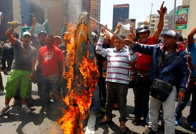 Supporters of the late President Hugo Chavez burn a flag with an opposition leader's campaign logotipo during a 2013 protest in Caracas.