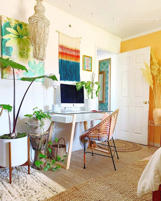 Boho office with rattan chair and multicolored fiber wall hanging