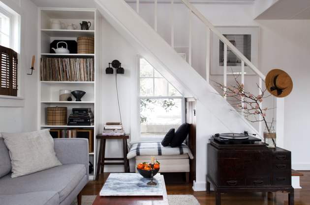 White painted stair rails in cottage living space with gray couch