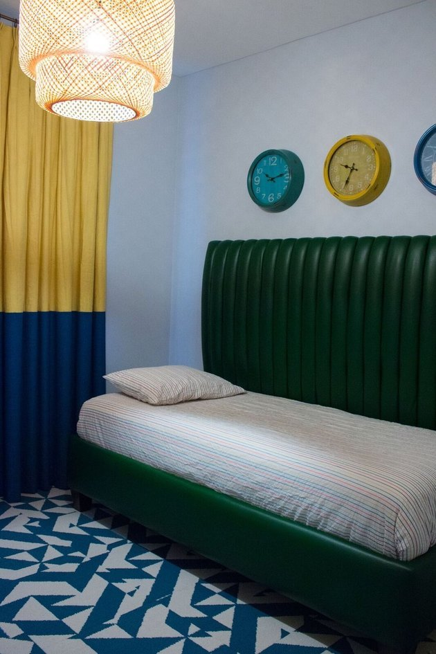 Blue and white tile floors, yellow and blue color block curtain, light cane pendant lamp, trio of clocks on wall, green leather day bed, striped bedding. Basement Bedroom Ideas