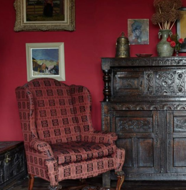 vermillion color patterned high back chair, dark red wall, dark wood credenza, art on walls.