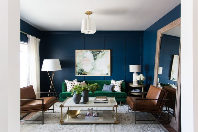 green living room idea with blue walls and velvet green sofa