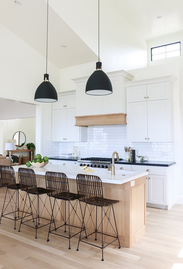 Industrial farmhouse kitchen with black pendant lights and linear bar stools