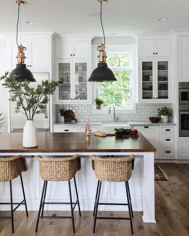 Industrial farmhouse kitchen with black metal pendant lights and seagrass bar stools