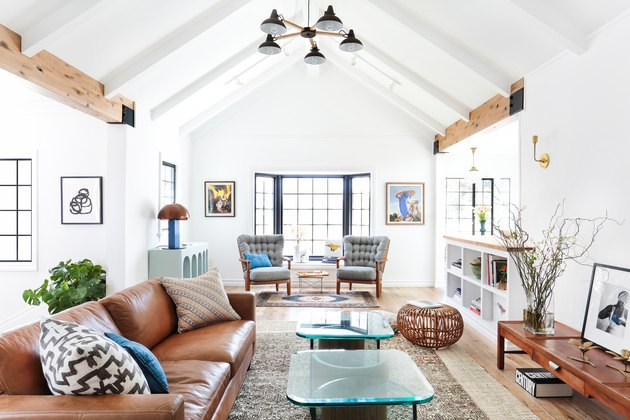 white living room layout idea with A-frame ceiling and midcentury furniture