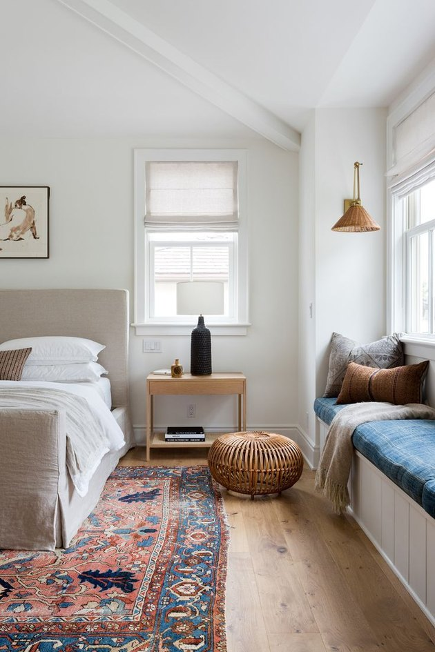 white bedroom color idea with colorful rug and blue window seat