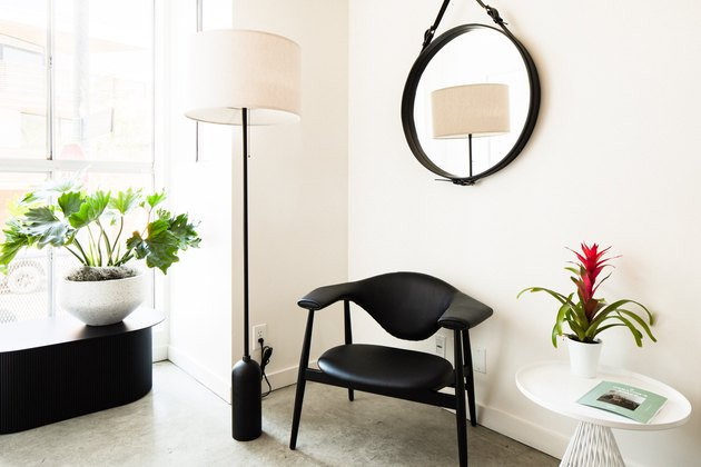 Black chair, black round mirror, plant and lamp