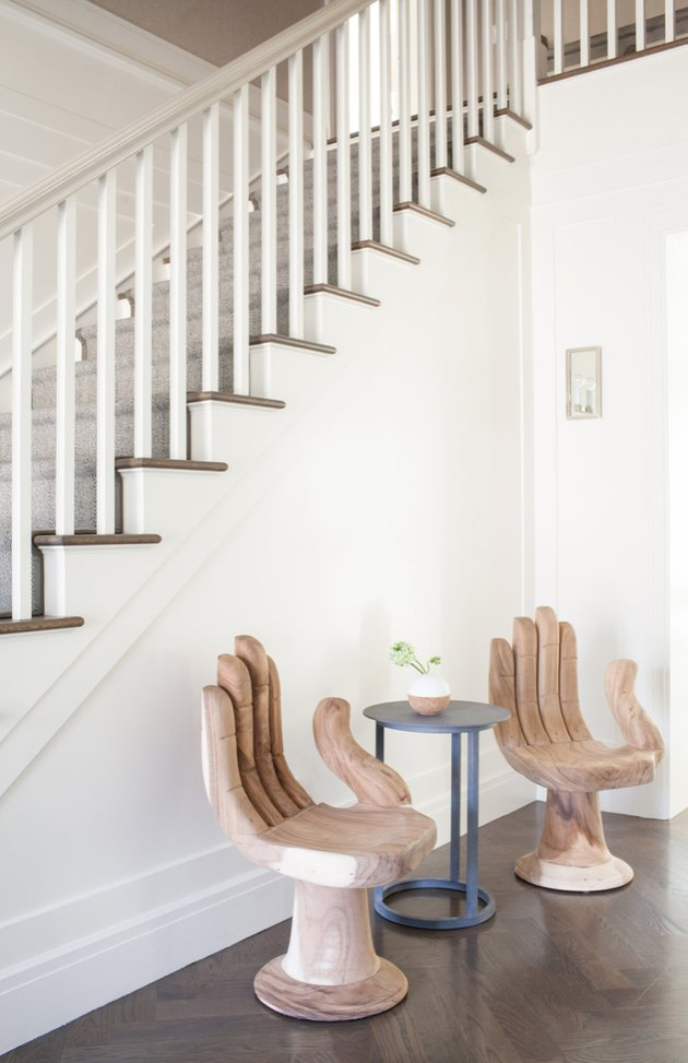 Entryway with modern chairs, table, stairway.