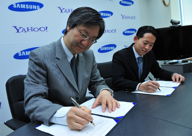 Dr. Ho Soo Lee, EVP, Media Solution Center, Samsung Electronics (L) and David Ko, SVP, Audience, Mobile and Local, North America, Yahoo! (R), sign strategic global partnership to pre-load Yahoo! services on tens of millions of Samsung devices. (Photo: Business Wire)
