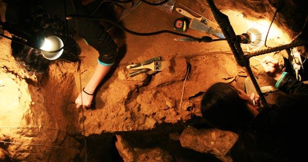 Dos científicos trabajan en en el yacimiento de El Sidrón.