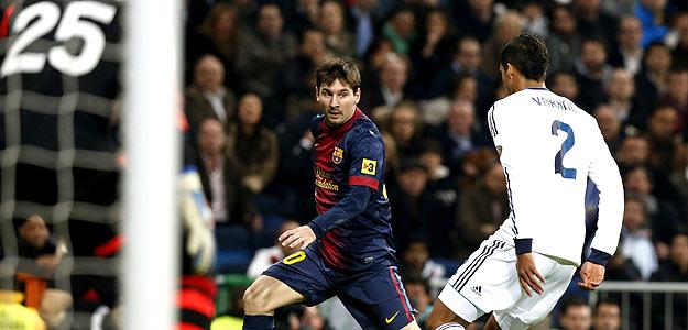 El delantero argentino del F.C. Barcelona Lionel Messi con el balón ante el defensa francés del Real Madrid Raphael Varane.