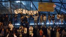 Varios manifestantes colocan una pancarta en la salida del metro de Sol