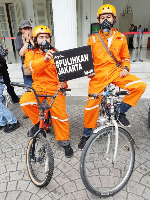 Mari kita bersihkan: pesepeda yang memakai alat pengaman dan masker pernapasan memimpin serah terima notifikasi gugatan perdata dari gerakan sosial yang disebut Gerakan Ibu Kota kepada pemerintah Jakarta di Balaikota, Jakarta Pusat, pada hari Rabu.