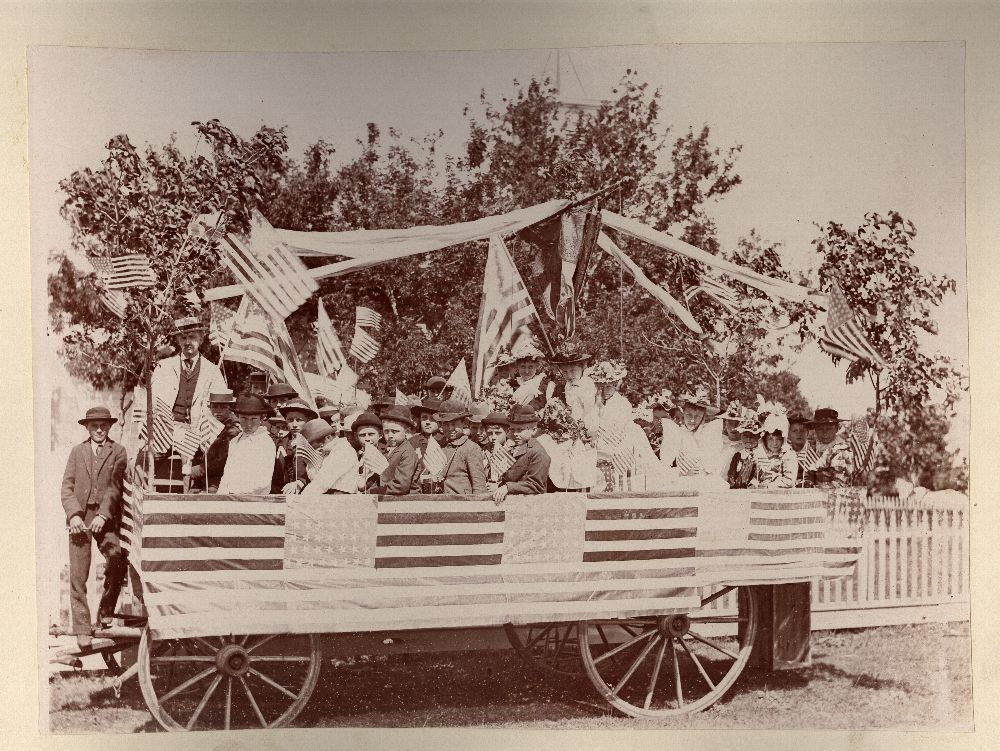 John Christoph photograph album - Children riding on a flag covered parade float, Ellinwood, Kansas.