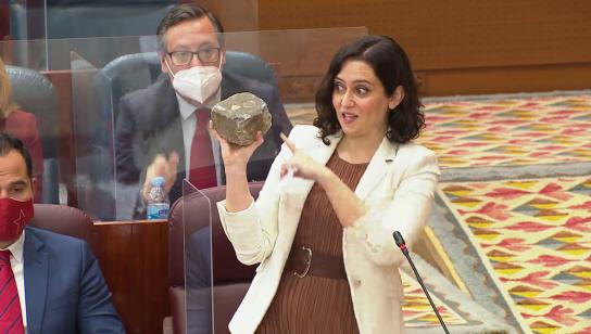 """Ayuso exhibe un adoquín de las protestas en la Asamblea y pregunta a Isa  Serra: """"¿Nos pegaría un tiro en la nuca?"""""""