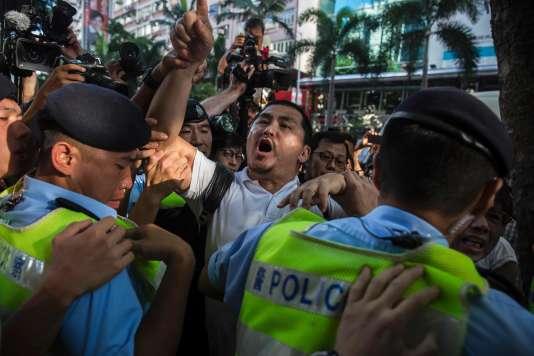 Un manifestant pro-Chine repoussé par les policiers, à Hongkong, samedi 1er juillet.