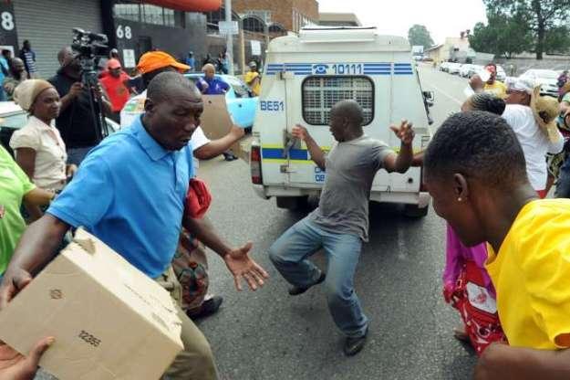 Des manifestants reconstituent le moment où Mido Macia, un chauffeur de taxi mozambicain, a été traîné par un véhicule de la police sud-africaine avant de succomber à ses blessures, à Benoni, le 8mars 2013.