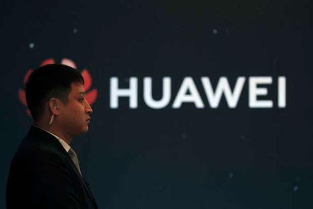 Membre d'un service de sécurité devant le logo de la compagnie chinoise Huawei, à l'occasion d'un lancement de produits, à Pékin, le 9 janvier 2019.