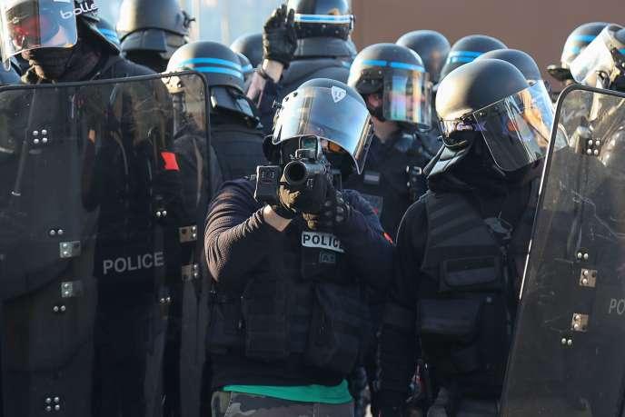 Un policier en civil muni d'un lanceur de balle de défense(LBD40)lors de la manifestation des« gilets jaunes» à Paris, le 23 février.