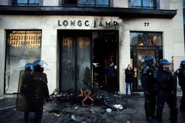 Des policiers se tiennent devant un magasin incendié après la manifestation des « gilets jaunes»,samedi 16 mars 2019 à Paris.