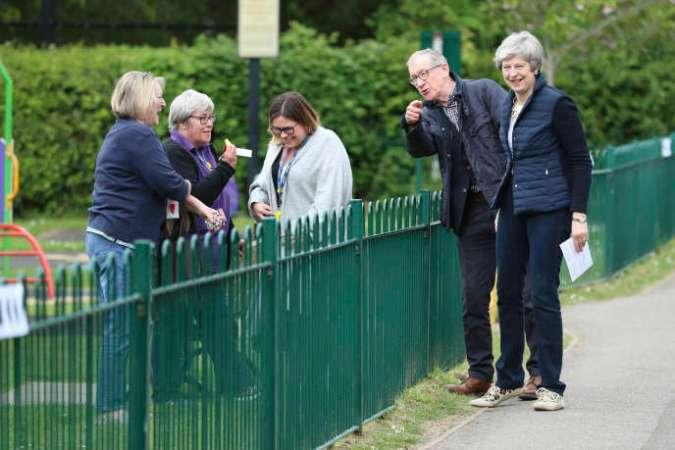 La première ministre, Theresa May, et son mari, Philip, en chemin vers leur bureau de vote, dans la vallée de la Tamise (sud-est de l'Angleterre), le 2 mai 2019.