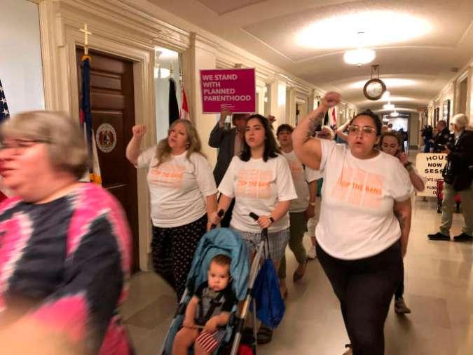 Des manifestants défilent dans les couloirs du Capitole du Missouri, vendredi17mai2019, à Jefferson City, en opposition à la législation interdisant l'avortement à huit semaines de grossesse.