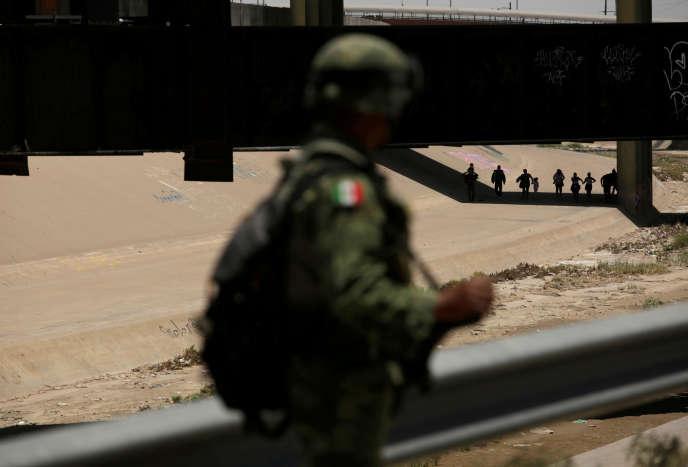 Ein Mitglied der mexikanischen Nationalgarde beobachtet Migranten aus Ciudad Juarez (Mexiko), die in El Paso (Texas) spazieren, nachdem sie am 21. Juni die Grenze illegal überquert hatten.